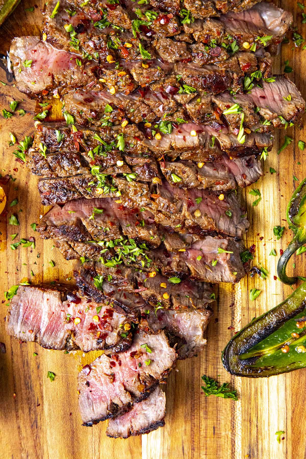 Sliced London broil on a platter with chili flakes