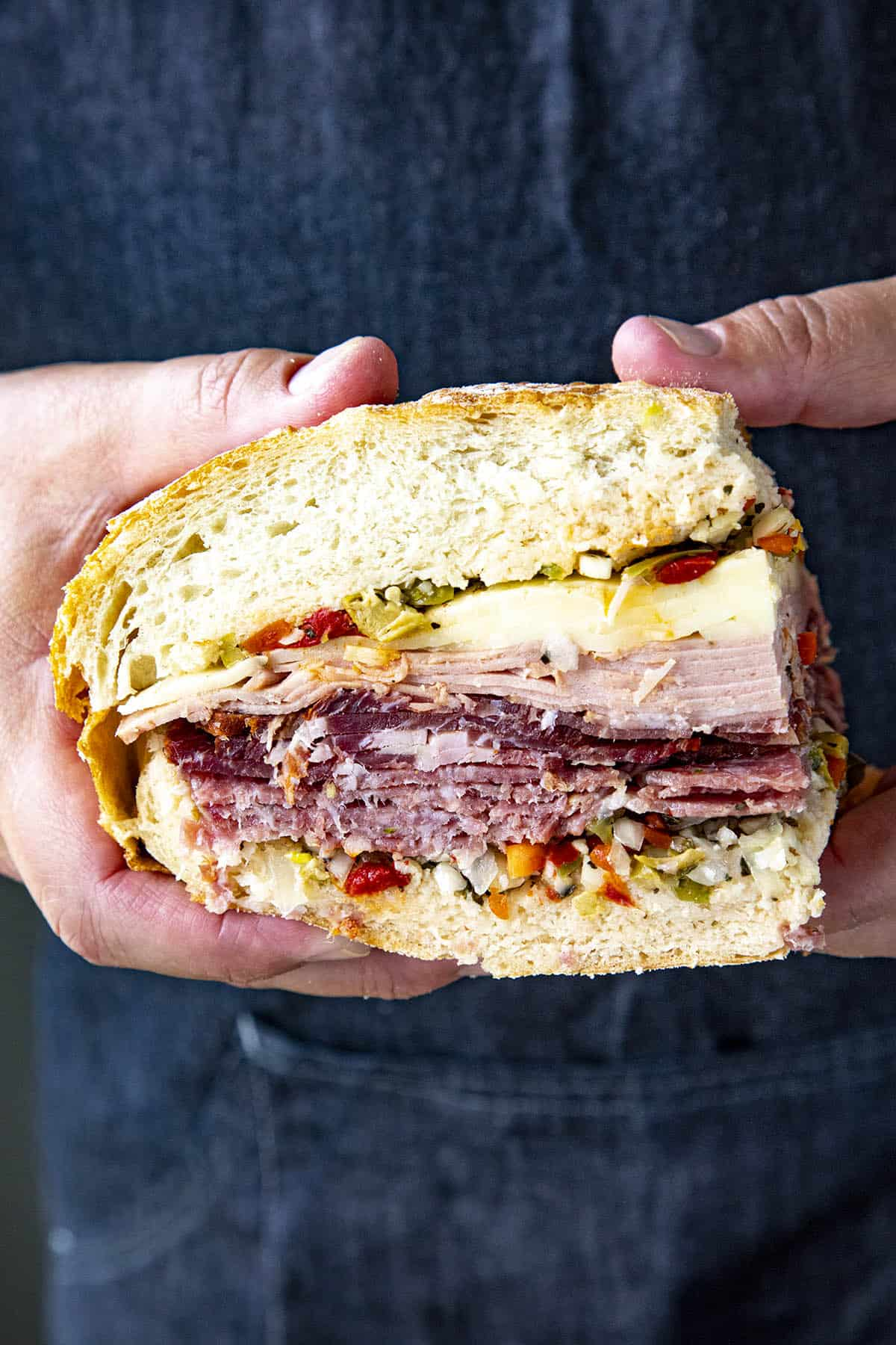 Mike holding a slice of a Muffaletta sandwich