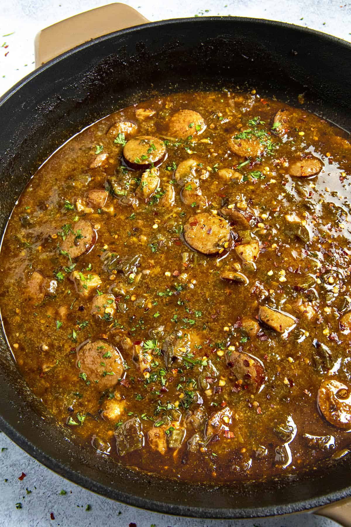 Cajun Chicken and Sausage Gumbo in a pot with garnish