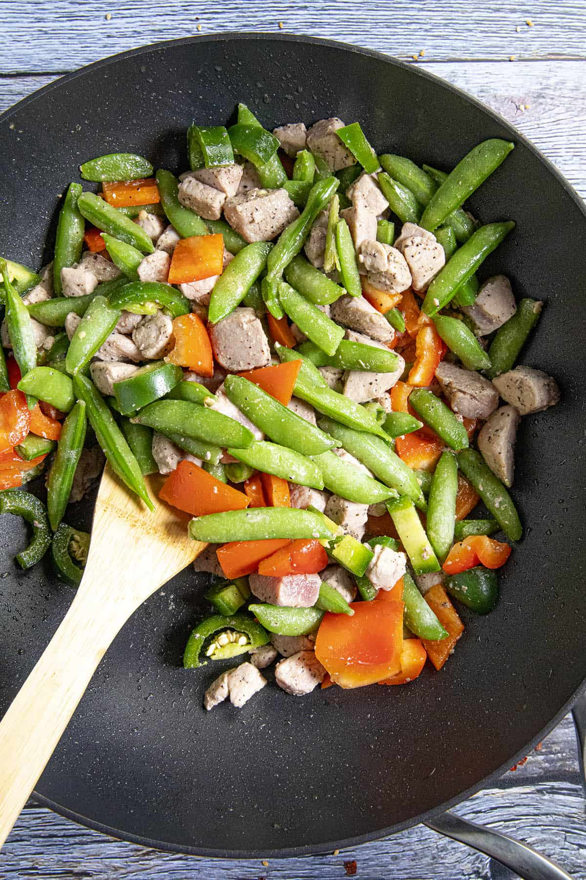 Stir frying the vegetables in a hot wok with the pork