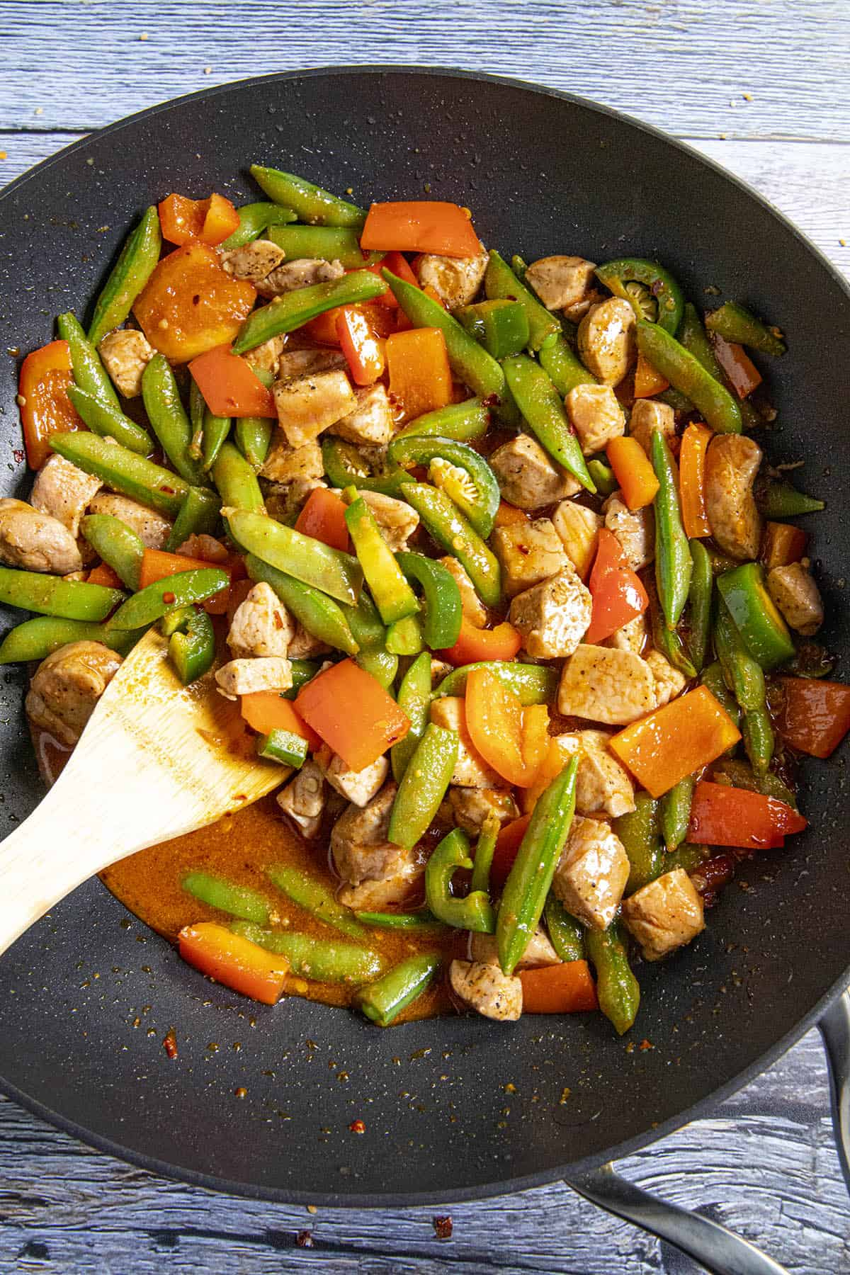 Stirring the stir fry sauce into the pan with the pork and vegetables
